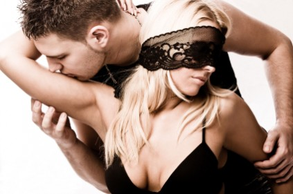 Man kisses arem from behind of woman in blindfold