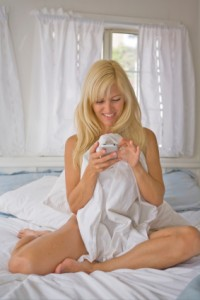 Blonde woman on bed playing with phone half naked