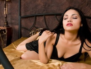 Good looking older woman leans forward on a bed, on a black bra