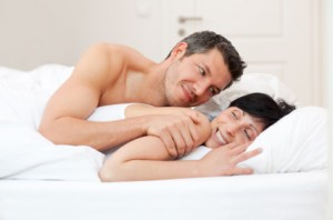 Man cuddles up to woman in bed