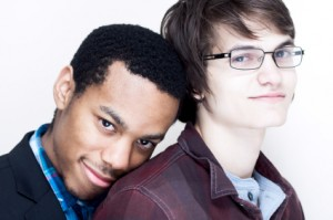 A gay black man stands behind a gay white man