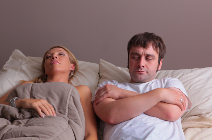 Man in bed while woman sleeps