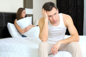 Man sits on the side of the bed, while woman sits in bed holding pillow, both unhappy