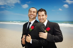 Two gay men holding each other on a beach getting married