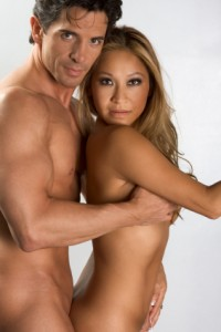man holds woman from behind, both naked and looking at the camera