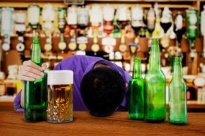 A man lies on bar surrounded by beer bottles