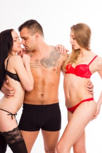Man stood up with two women, one in black lingerie and one in red