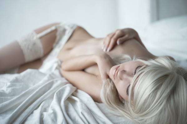 Blonde woman leans back in bed