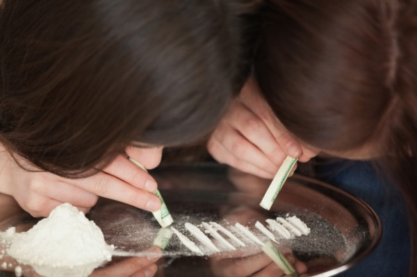 Two brunettes snorting coke