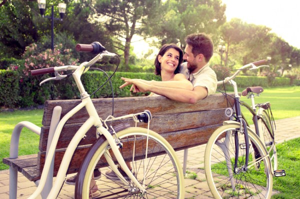 Couple in love sitting together on a bench with bikes beside