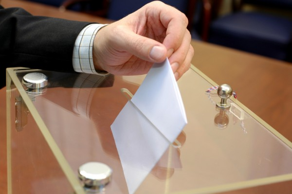 Man placing vote in box