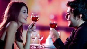 Young happy amorous couple celebrating with red wine at restaura