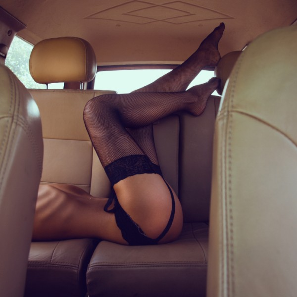 Woman in stockings in back of her car