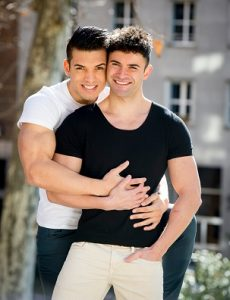two happy gay men hold each other