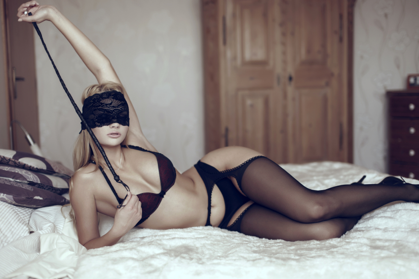 blindfolded half naked woman on bed