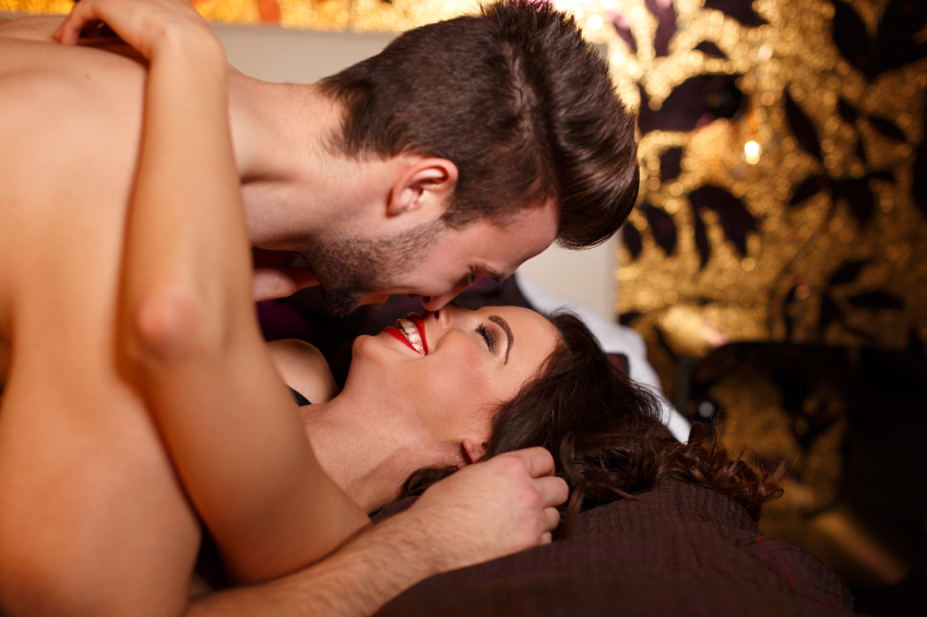 Passionate couple laying and kissing on bed