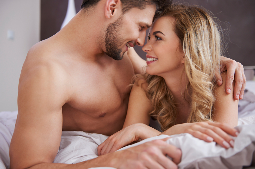 A sexy man and a sexy woman lie in bed together