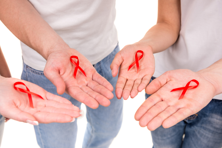 Close-up of hands holding red ribbons to rise AIDS HIV awareness.