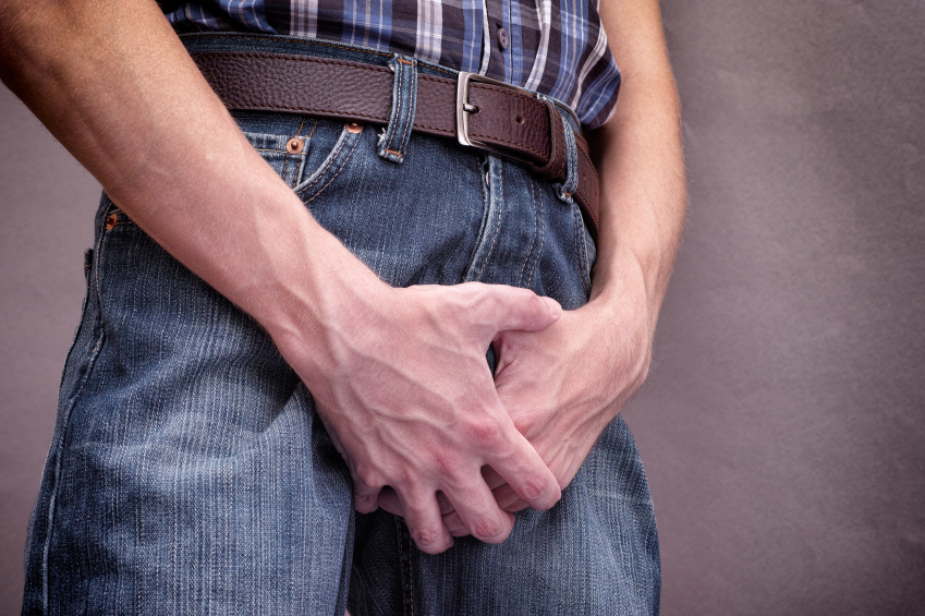 Man in jeans covers his crotch with hands.