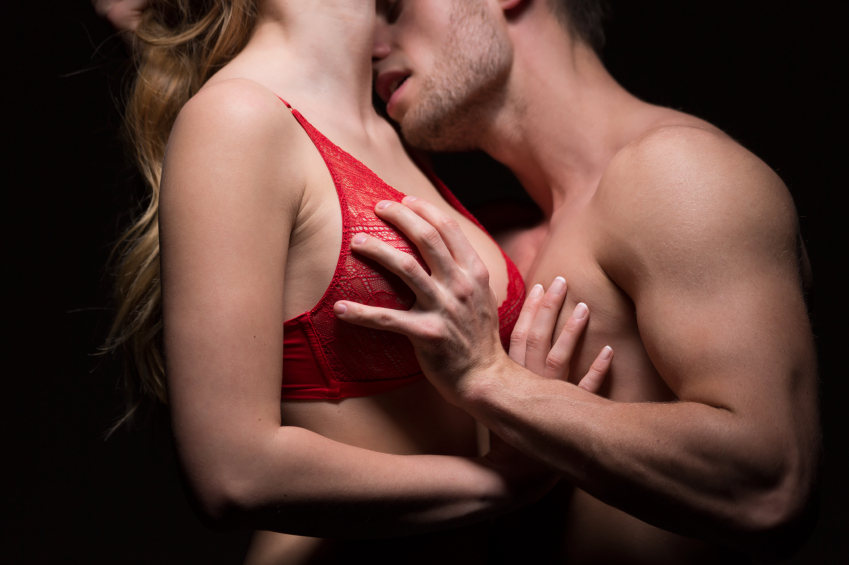 man and woman kiss as he holds her breast