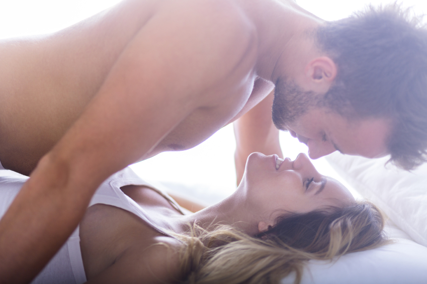 A passionate couple in bed trying out their sex schedules