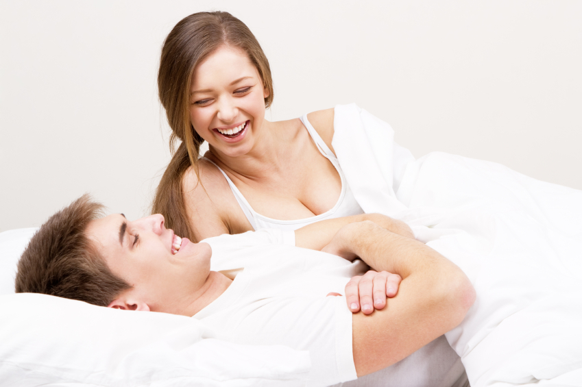 woman laughs in bed with a man