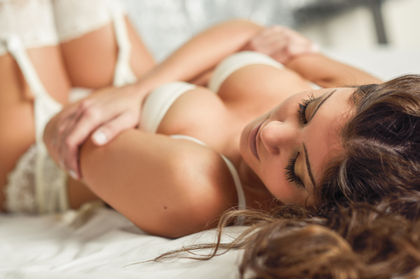 Sexy woman lying down in her lingerie, looking at her phone off camera for some escort safety tips