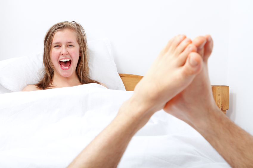 Happy woman getting oral sex in bed.