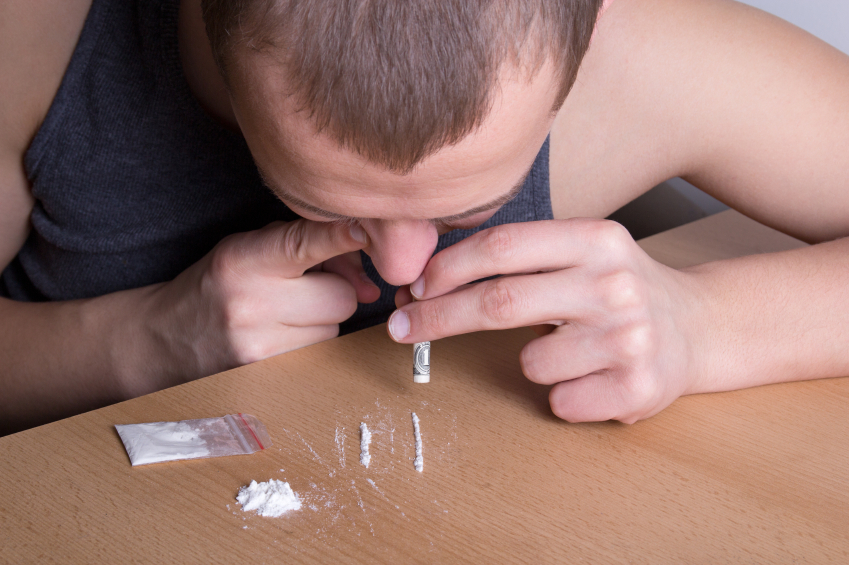 man snorting drugs off a table