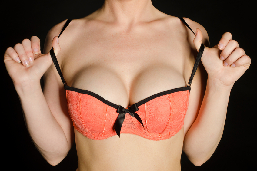 close up of woman holding bra with big breasts