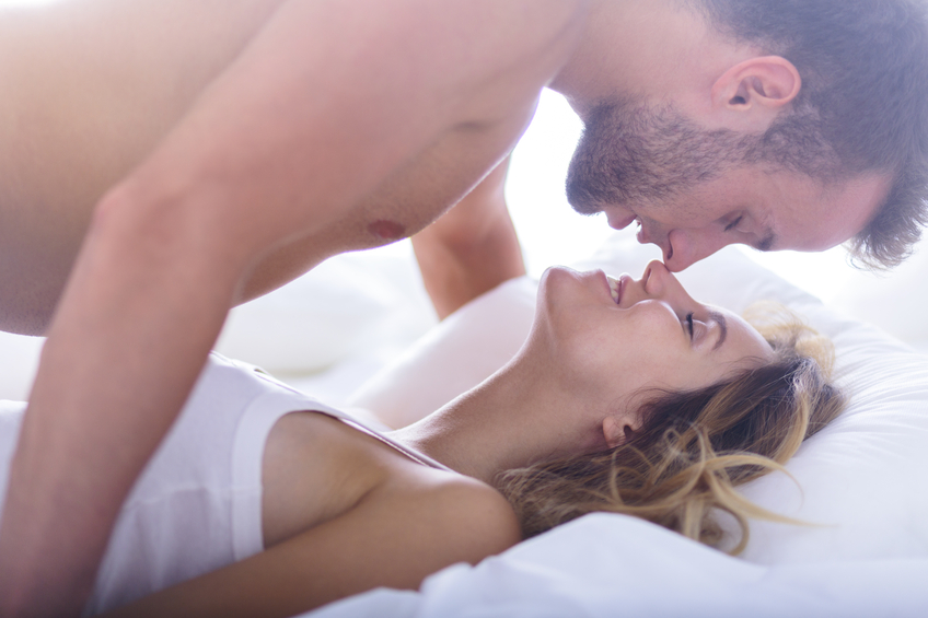 man in missionary position with woman in bed