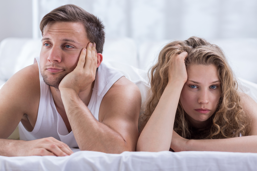Young bored couple having problems in bedroom