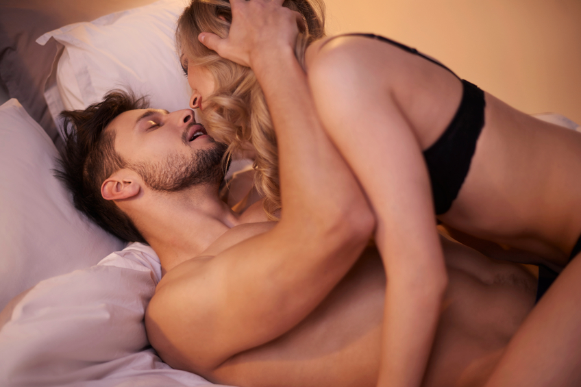 Passionate couple in the bedroom, woman on top of man