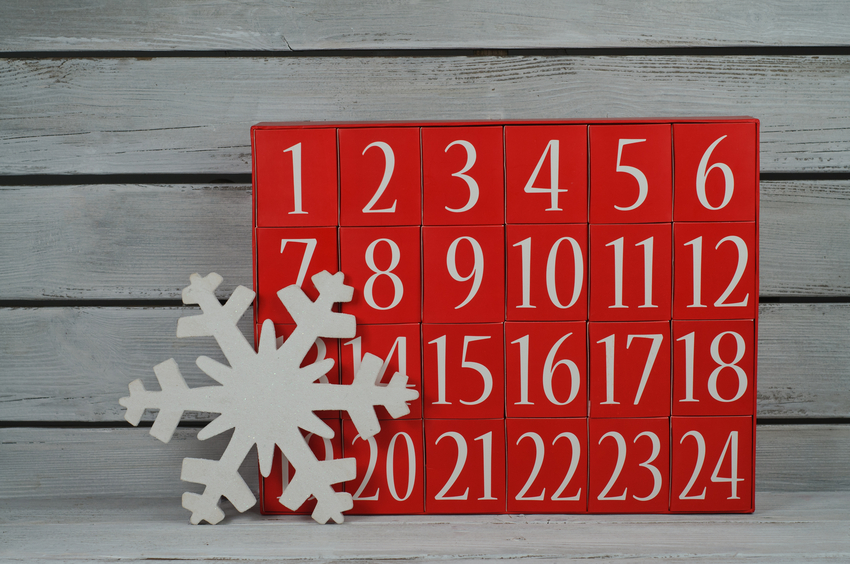 Advent calendar and snowflake on white wooden background