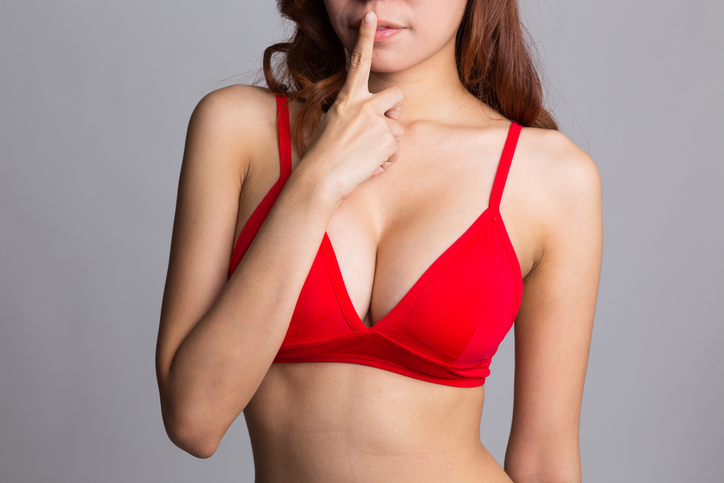 Woman in red bra with finger over her mouth