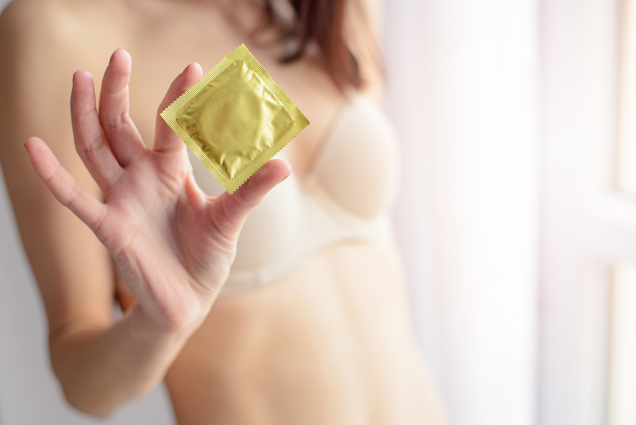 Woman in underwear with condom for safe sex