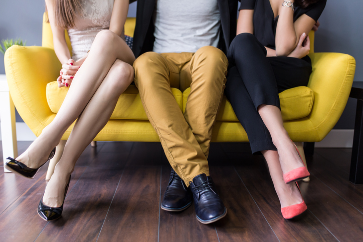 Man on couch with two women symbolising a threesome