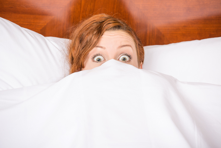 Shocked woman in bed