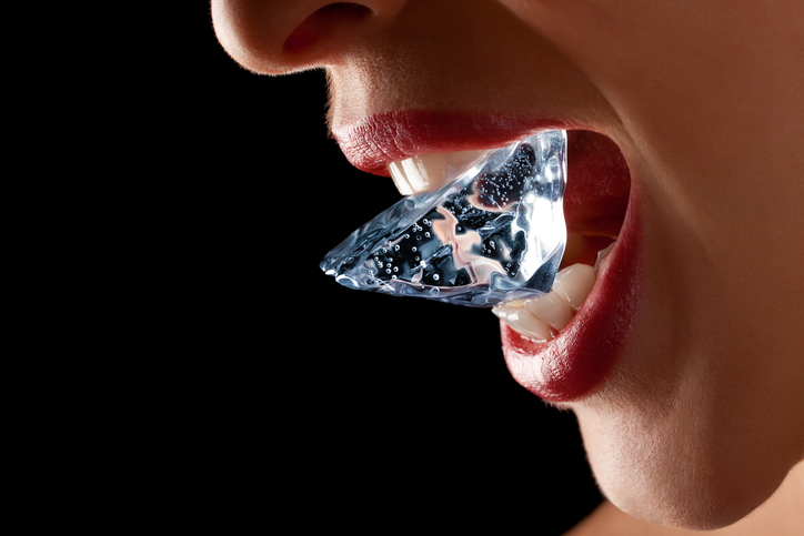 Ice cube in a woman's mouth against black background.