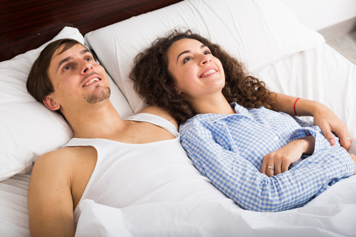 Couple leaning back satisfied on bed