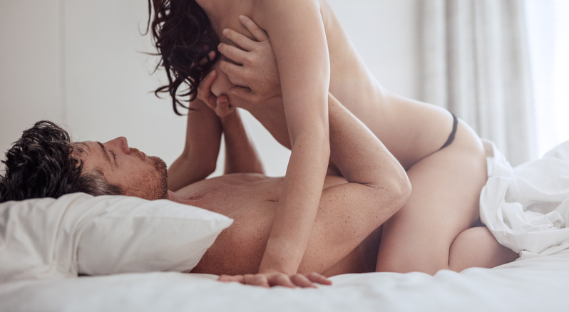 Intimate couple making love in bedroom. Young couple having sex in bed with man lying and woman on top.