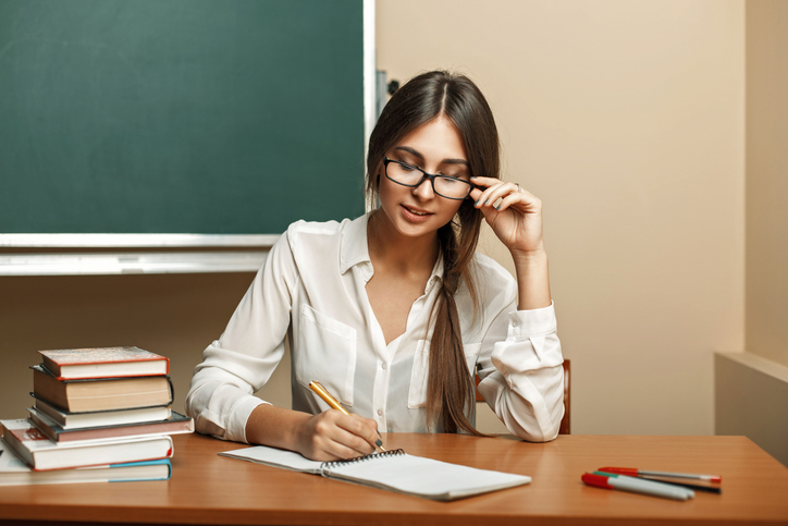 Beautiful young woman with glasses to study at university, reading books and writes in a notebook.