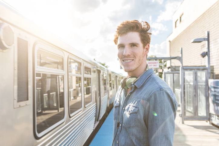 Young man at train or subway station on a sunny day in Chicago. Portrait of a ginger young man looking at camera with a blurred train moving on background.