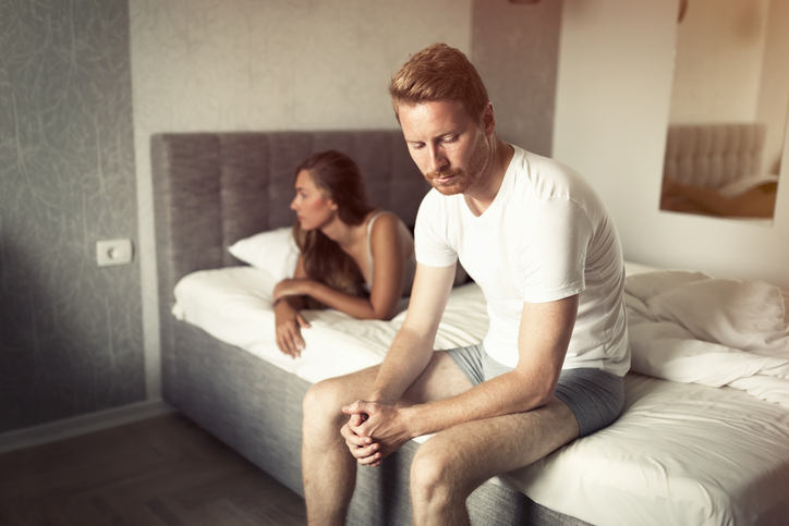 Couple on bed looking unhappy