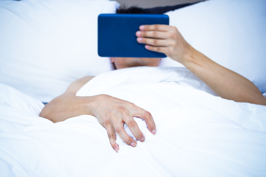 Young asian man lying on white bed & watching pornography on computer tablet. focus to right hand