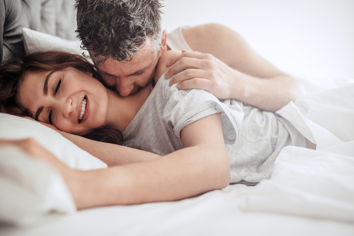 Beautiful passionate couple having sex on bed. Man kissing on neck of woman, both lying on bed.