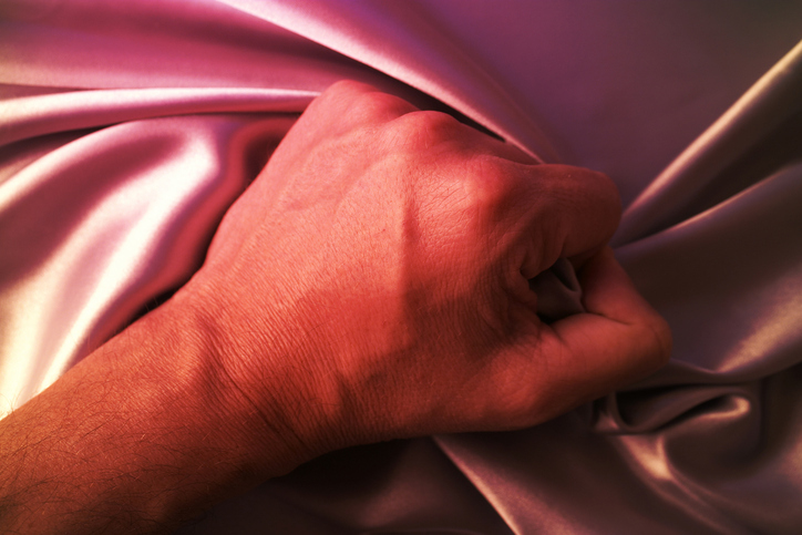 Man grabbing satin sheet on the bed.