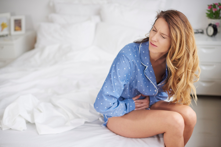 woman holding her stomach  on her bed having a period