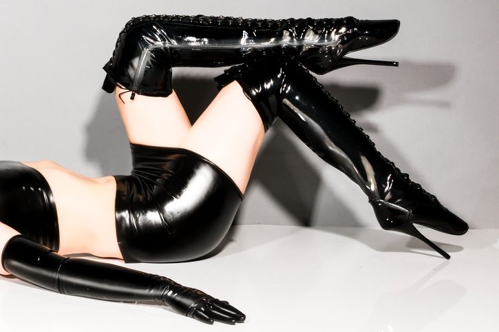 Adult woman wearing black shiny latex dress and overknee boots with extreme ballet heels.