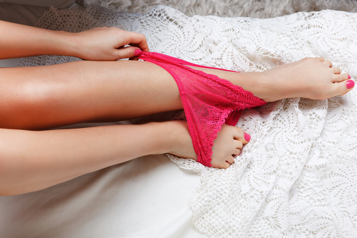 Close-up of sexy pink panties on a woman's feet